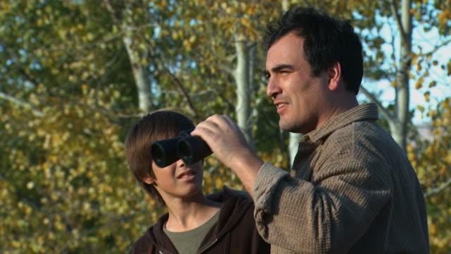 man and boy looking through binoculars - bird watching stock videos & royalty-free footage