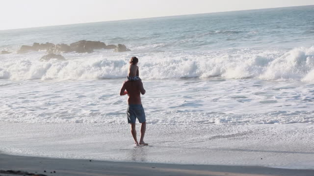 vidéos et rushes de ms man and boy on beach looking out at wave break with seamist in air / montezuma, puntarenas, costa rica - kelly mason videos