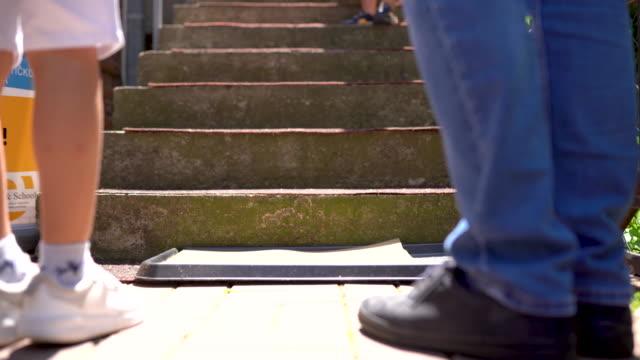 階段を上る前に消毒ドアマットに立っている男と少年 - ラグ点の映像素材/bロール