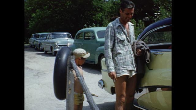 1952 MONTAGE Man and boy with inner tube, near cars / Grand Bend, Ontario, Canada