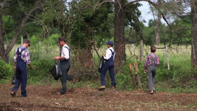 ms pan man and boy working at farm / manitoba community, close to santa cruz de la sierra, bolivia - dungarees stock videos and b-roll footage