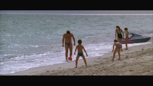 ws zi man and boys playing with beach ball on beach / miami, florida, usa - anno 1994 video stock e b–roll