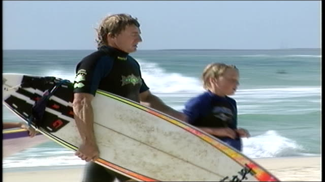 man and boys walking with surf and boogie boards on beach in wetsuits in perth australia - water sports equipment stock videos and b-roll footage