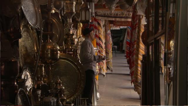 man and child examine metalwork wares in curiosity shop in morocco - casablanca, morocco - metalwork stock videos & royalty-free footage