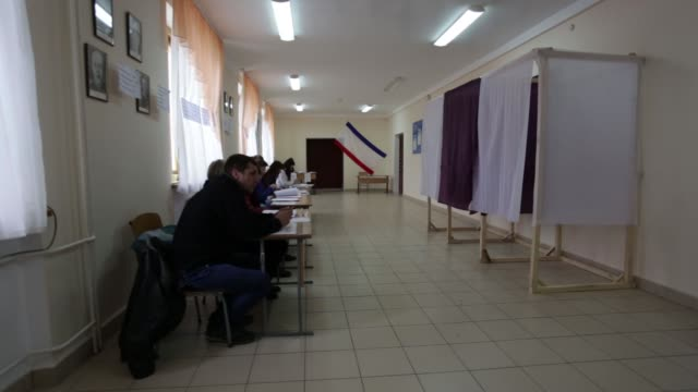 man and child head to polling place, various shots of cars, flags, interior of polling place with poll workers and no voters, ukrainian flag colored... - röstsedel bildbanksvideor och videomaterial från bakom kulisserna
