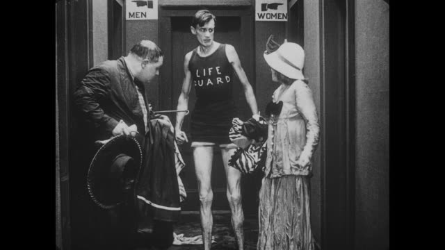 1917 Man (Fatty Arbuckle) and date (Alice Mann) laugh at tall lifeguard in bathhouse