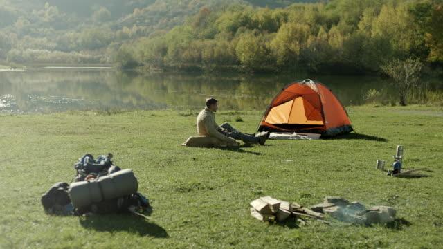 stockvideo's en b-roll-footage met man en hond zittend naast tent aan het meer - tent