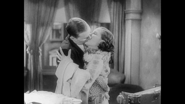 1931 man (pat o' brien) and fiance (mary brian) sing and kiss as they pack clothes - 1931 stock videos & royalty-free footage