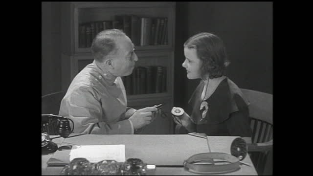 man and girl talking behind office desk, and hands turning handset of telephone; girl with earpiece and holding the other end of the earpiece in her... - 1940 1949 stock videos & royalty-free footage
