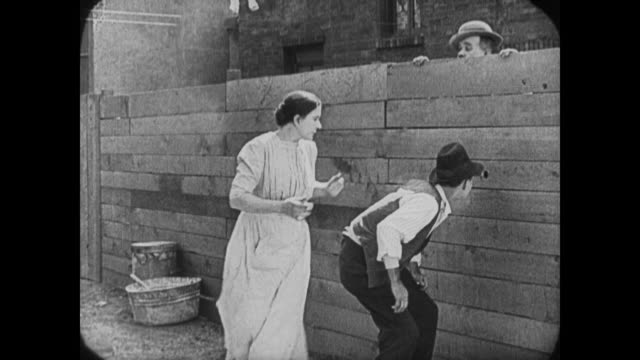 1920 man (buster keaton) and girlfriend caught in garden by angry parents before man's mother and girlfriend's father are both caught peeping through fence hole by irate spouses - buster keaton stock videos and b-roll footage