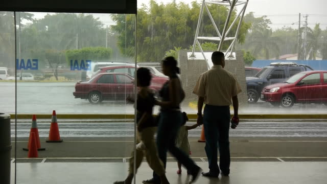 a man and his daughter watch the rain from inside the managua international airport. - managua stock-videos und b-roll-filmmaterial