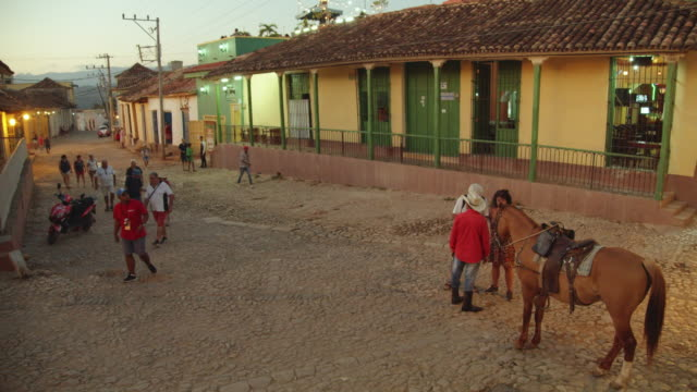 man and his horse on a touristy cobblestone street in trinidad, cuba - kopfsteinpflaster stock-videos und b-roll-filmmaterial