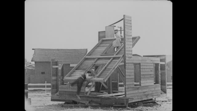 1920 man (buster keaton) and his newlywed narrowly miss being injured by an unstable wall that keaton just constructed, and a man changes numbers on wooden boxes - buster keaton stock videos and b-roll footage
