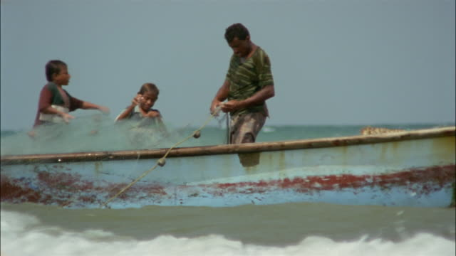 vidéos et rushes de a man and his sons pull fishing nets onto their small boat. - pêcheur