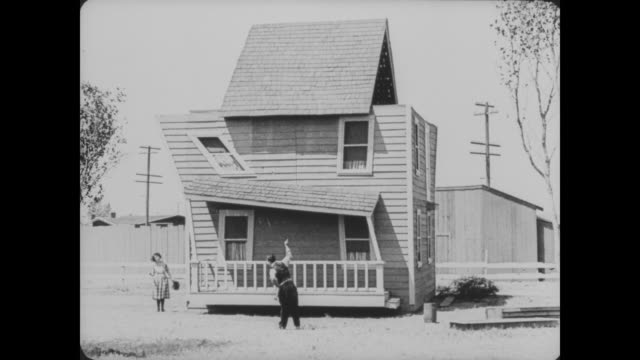 1920 man (buster keaton) and his wife (sybil seely) look at their finished house questioning why it is askew - silent film stock videos & royalty-free footage