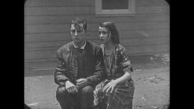 stockvideo's en b-roll-footage met 1920 man (buster keaton) and his wife (sybil seely), upset, sit in front of their spinning house - tegenspoed