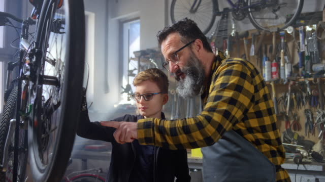 slo mo man and his young son checking the chain on a bike in the workshop - skill stock videos & royalty-free footage