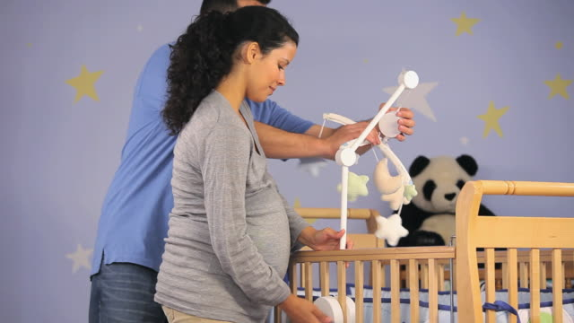ms tu man and pregnant woman putting together crib in nursery room / richmond, virginia, usa.  - nursery bedroom stock videos & royalty-free footage