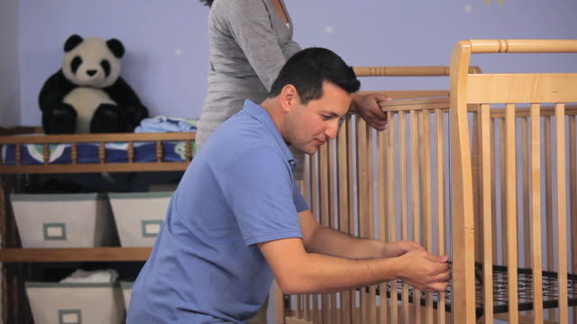 vídeos y material grabado en eventos de stock de ms pan tu man and pregnant woman putting together crib in nursery room / richmond, virginia, usa.  - cuna