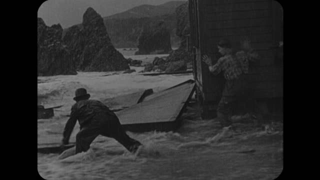 1916 man and smugglers attempt to break into house during storm as house begins to float out to sea - 1916 stock videos & royalty-free footage