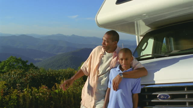 ms man and son posing against parked motor home and observing landscape / asheville, north carolina, usa - familie mit einem kind stock-videos und b-roll-filmmaterial