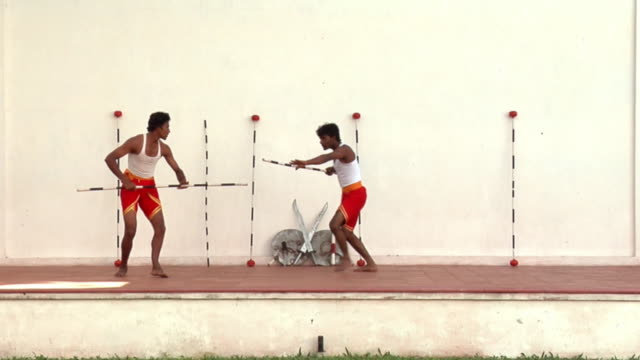 WS Man and teen boy performing martial arts with sticks / Cochin, Kerala, India