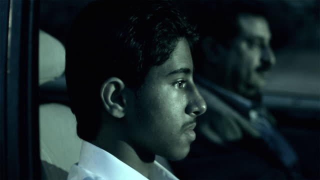 CU R/F Man and teenage boy (14-15) traveling in car at night / New York City, New York, USA