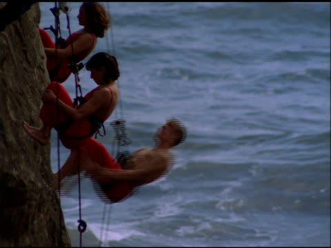 A man and two women dressed in red outfits and wearing harnesses perform dance on cliff face, Project Bandaloop, California