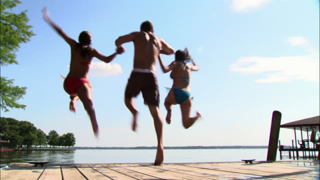 ws man and two women holding hands and jumping off dock into lake/ texas - male with group of females stock videos & royalty-free footage