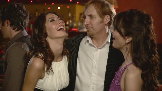 stockvideo's en b-roll-footage met cu tu man and two women relaxing in bar, jacksonville, florida, usa - man met een groep vrouwen