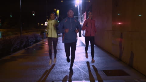 ts man and two women running in the city at night - 30 39 years stock videos & royalty-free footage