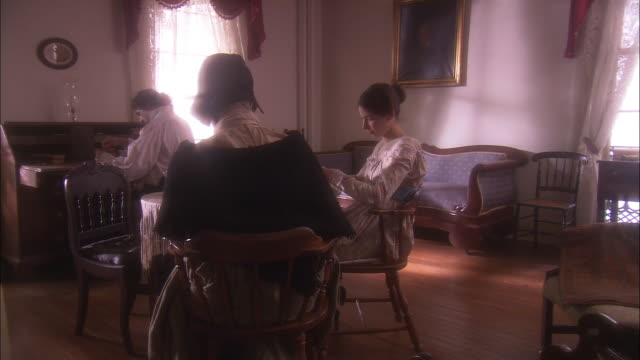 a man and two women sit in a 19th century sitting room. - reenactment stock videos & royalty-free footage