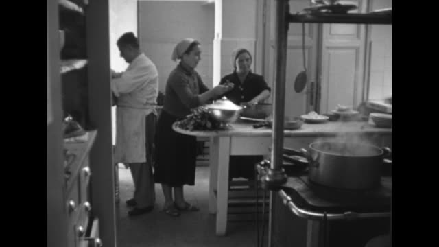 man and two women working in kitchen preparing food / boiling food in pot / pots on top of stove, man in background waiting / close view of chef... - 追放点の映像素材/bロール