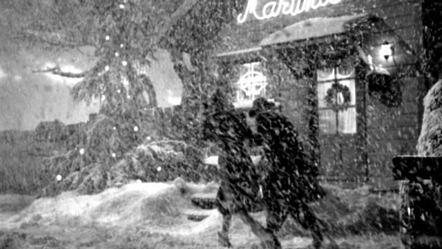 vídeos de stock e filmes b-roll de a man and woman approach a cozy cafe in a blizzard. - 1946