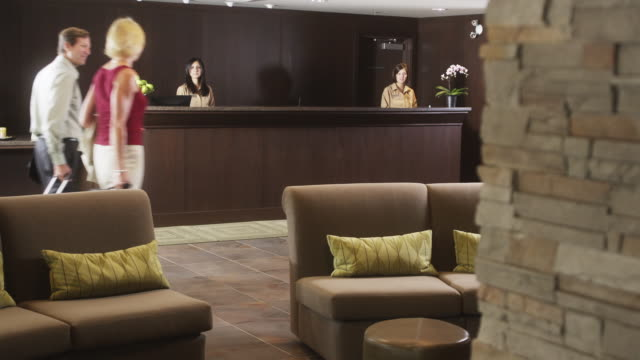 WS man and woman approaching hotel reception desk / Squamish, British Columbia, Canada