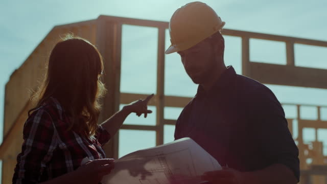 man and woman architects looking at blueprints and inspecting construction site - construction worker stock videos and b-roll footage