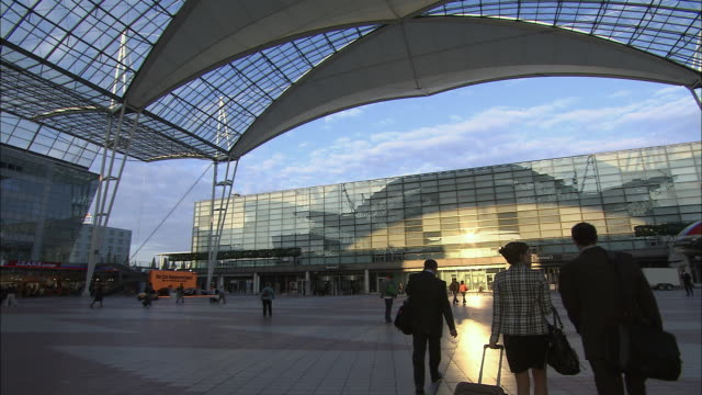 stockvideo's en b-roll-footage met ws man and woman arriving at modern airport/ munich, germany - münchen vliegveld