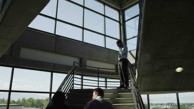 WS DS Man and woman ascending office stairs, other man talking on mobile phone / Orem, Utah, USA