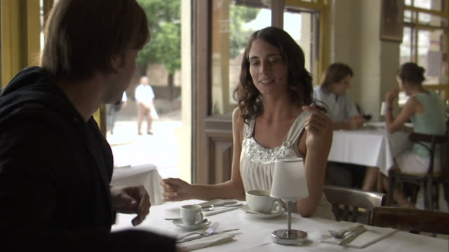vidéos et rushes de ms man and woman at cafe table as serving brings espresso to man/ man and woman talking/ buenos aires, argentina - veste et blouson
