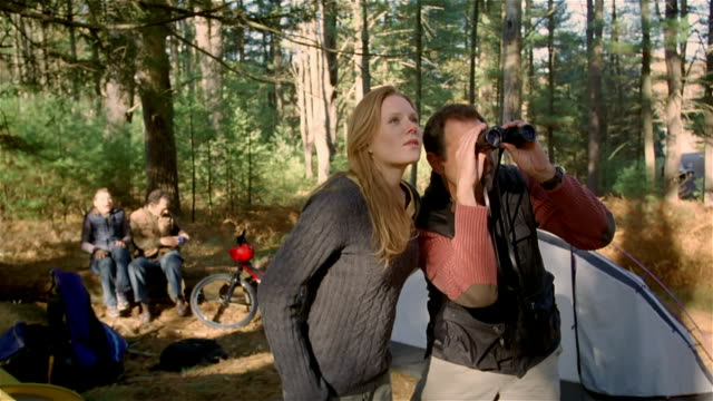 vídeos de stock e filmes b-roll de man and woman birdwatching / passing binoculars back and forth and pointing / another couple joining them - observar pássaros