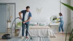 Man and woman busy with housework in bedroom cleaning room with vacuum cleaner