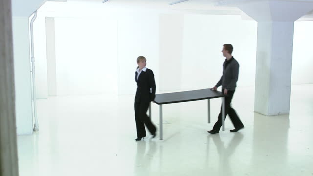 man and woman carrying a table in a white and empty office premises sweden. - veduta di interni video stock e b–roll