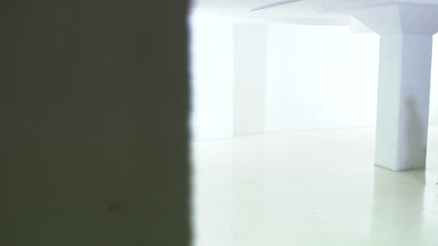 man and woman carrying a table in a white and empty office premises sweden. - stile minimalista video stock e b–roll
