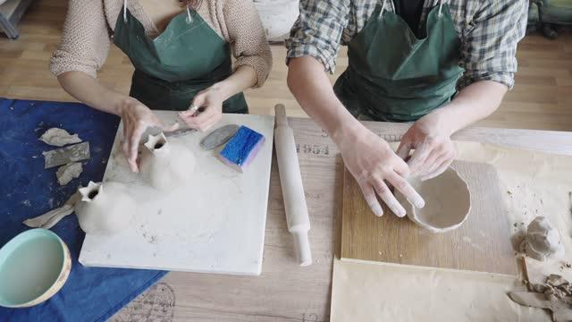vídeos de stock, filmes e b-roll de homem e mulher ceramistas trabalhando juntos em seu estúdio - desenhar atividade