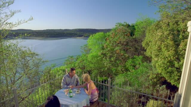 ms zi cs slo mo man and woman chatting at table outdoors / canyon lake, texas, usa - canyon lake stock videos & royalty-free footage