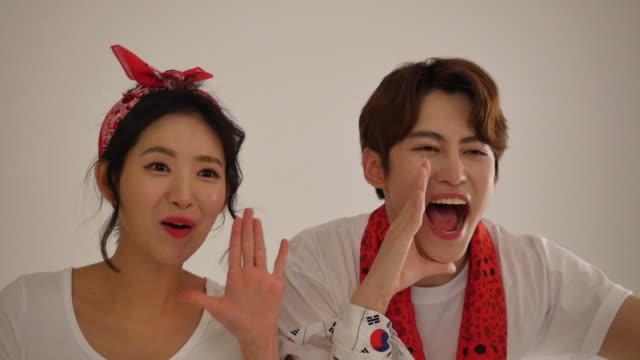 man and woman cheering for south korean soccer team - internationaler fußball stock-videos und b-roll-filmmaterial