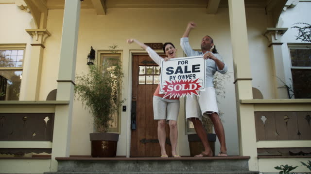 WS Man and woman cheering on porch holding for sale sign / Seattle, Washington, USA