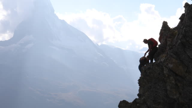 man and woman climb steep rock ridge, matterhorn distant - ridge stock videos & royalty-free footage