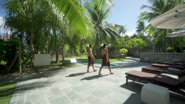 a man and woman couple and a hot tub hot tub spa, lifestyle at a tropical island resort. - spa stock videos & royalty-free footage
