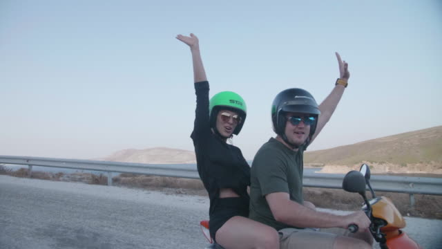 vidéos et rushes de man and woman couple arms up driving scooters motorbikes in skyros, greece. - bras en l'air
